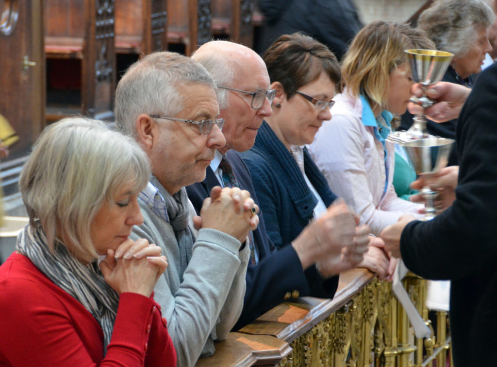 People kneeling taking communion