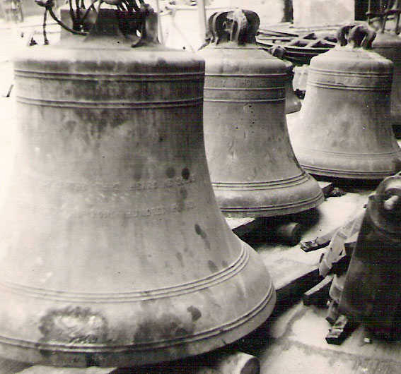 A black and white photo of huge bells on the ground