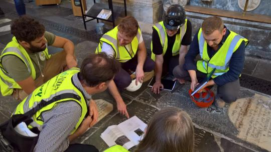 People in high-vis jackets and hard hats kneeling during a Behind the Scenes Tour at Bath Abbey