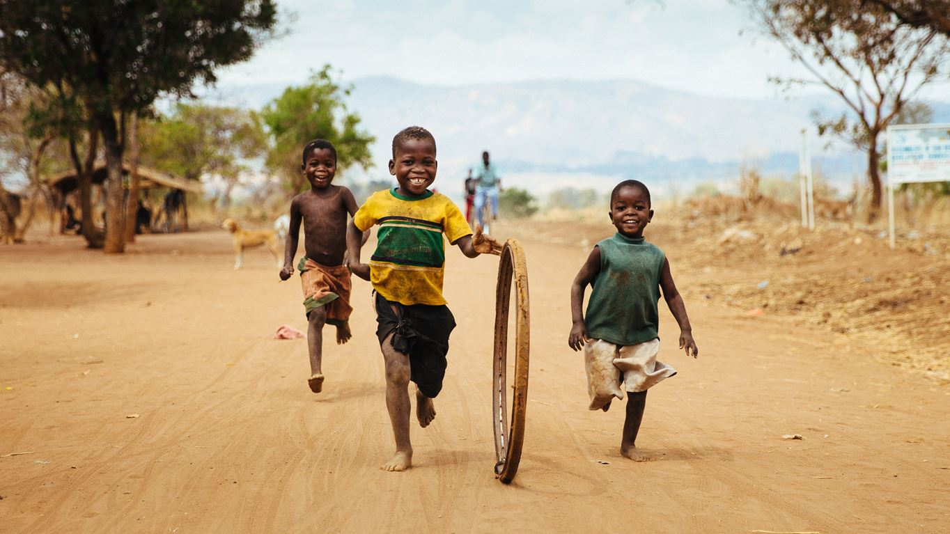 Children playing with a hoop on a rough track