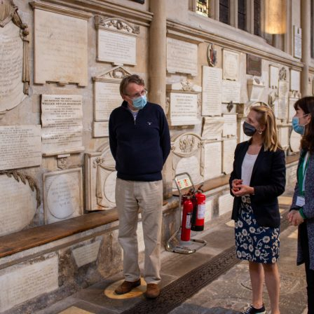 Rector of Bath Abbey Guy Bridgewater, Bath MP Wera Hobhouse and Polly Andrews, Learning Officer at Bath Abbey looking at the Abbey's memorials in the North transept