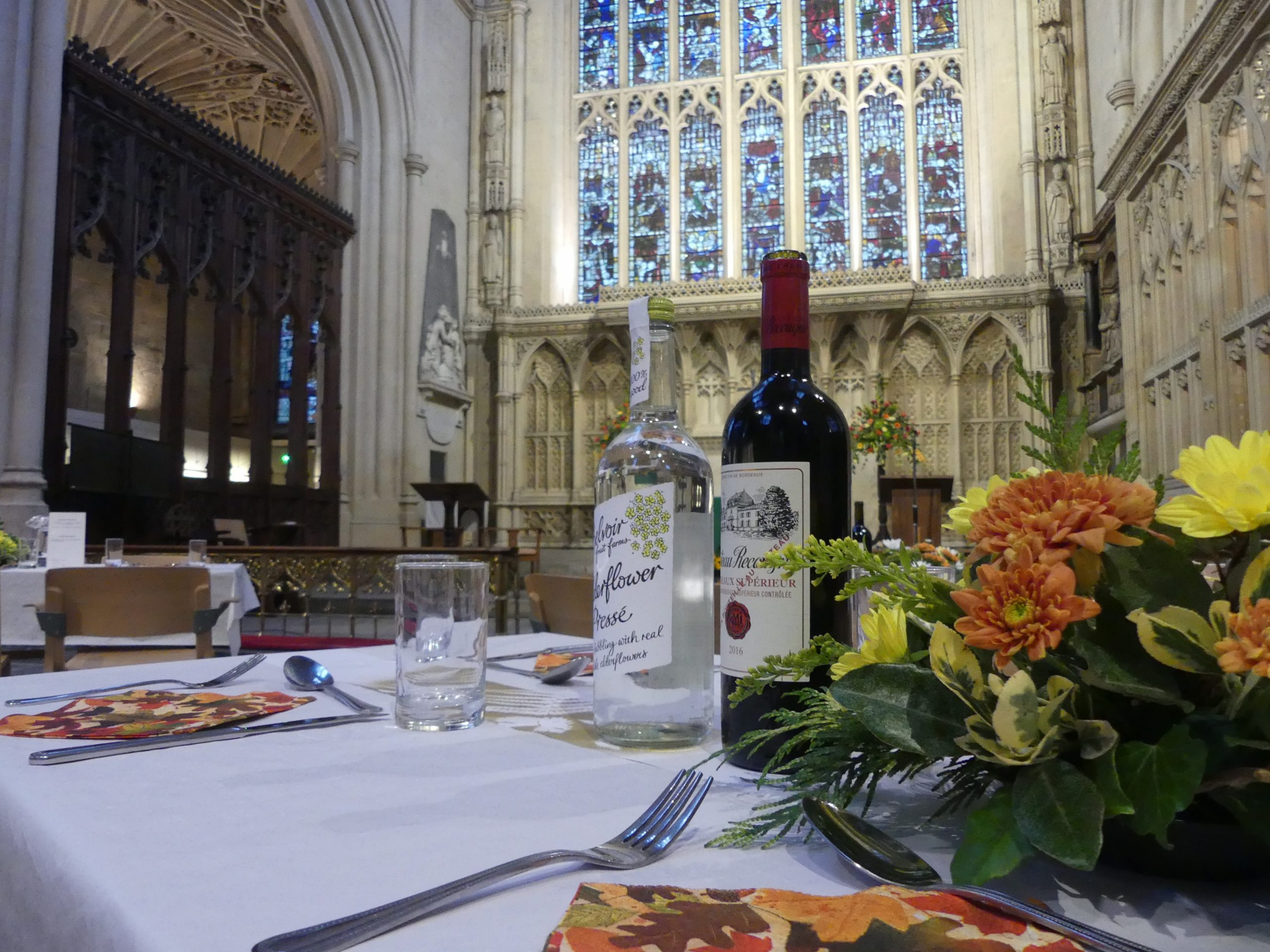 Table laid with two bottles of drink for Harvest Dinner in the foreground of Bath Abbey